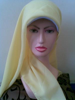 Tarik satu ujung jilbab kebelakang lilitkan di leher.